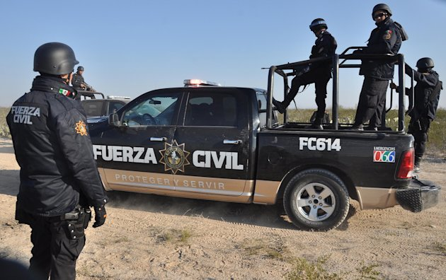 Nuevo Leon state police stand guard on a dirt road leading to a ranch near the town of Mina, in northern Mexico, Monday, Jan. 28, 2013. At least eight bodies were found in a well near this ranch on Su