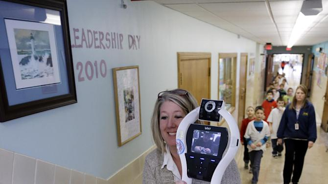 In this Thursday, Jan. 24, 2013 photo, Winchester Elementary School teacher Dawn Voelker carries a robot up the stairs that is being operated by Devon Carrow while he is attending school at in West Seneca N.Y. Carrow's life-threatening allergies don't allow him to go to school. But the 4-foot-tall robot with a wireless video hookup gives him the school experience remotely, allowing him to participate in class, stroll through the hallways, hang out at recess and even take to the auditorium stage when there's a show. (AP Photo/David Duprey)