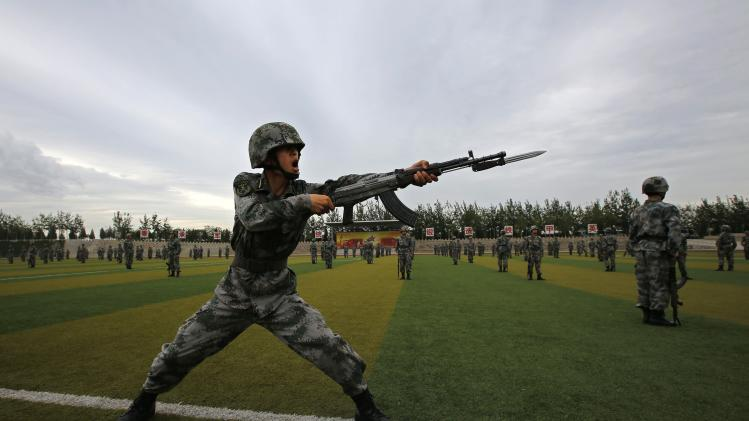 Soldiers of the People's Liberation Army (PLA) practise with guns in a drill during an organised media tour at a PLA engineering academy in Beijing