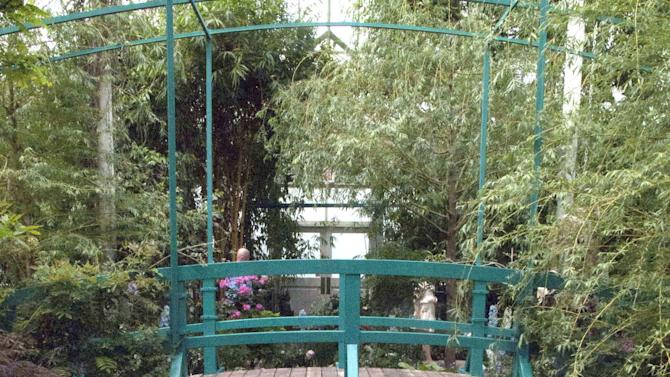 """In this May 26, 2012 photo, a replica of a bridge on the property of artist Claude Monet's home is featured in an exhibition at the New York Botanical Garden in New York.  """"Monet's Garden,"""" evokes the artist's garden at Giverny, his home in France from 1883 until his death in 1926. The exhibit runs through Oct. 21. (AP Photo/Ray Stubblebine)"""