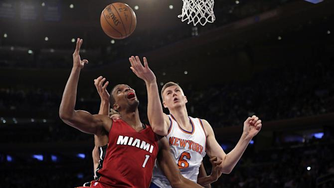 Miami Heat forward Chris Bosh (1) and New York Knicks forward Kristaps Porzingis (6) look for a rebound during the second half of an NBA basketball game at Madison Square Garden on Friday, Nov. 27, 2015, in New York. The Heat defeated the Knicks 97-78. (AP Photo/Adam Hunger)