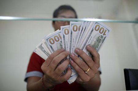 Bank staff shows U.S. hundred dollars bills at AYA Bank's money changer in Yangon