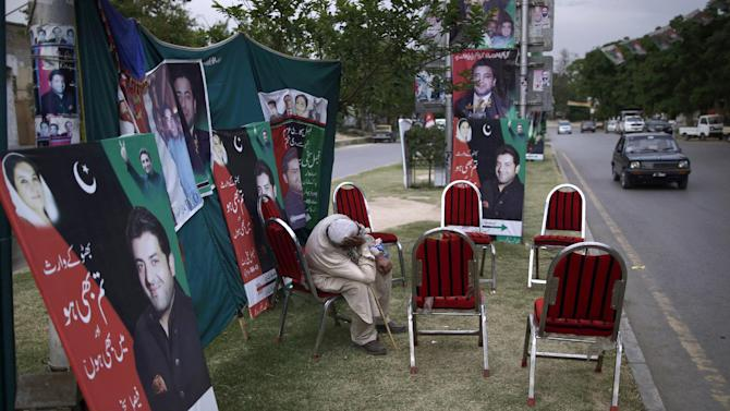 In this Tuesday, May 7, 2013, photo, a supporter of Pakistan People's Party (PPP), takes a nap while sitting in a street median next to banners showing candidates of the party for the upcoming parliamentary elections, in Islamabad, Pakistan. The campaign posters, fliers and commercials for the Pakistan People's Party are both advertisements for why the party has been so popular and indicate the challenges it faces in the May 11 election: two of the people on the posters are dead and another is not old enough to run in the election. (AP Photo/Muhammed Muheisen)