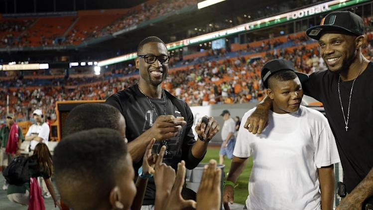 Miami Heat's Dwyane Wade, center, and Udonis Haslem, right, stand on the sideline as boys make the The U sign before an NCAA college football game against Florida State, Saturday, Oct. 20, 2012, in Miami. (AP Photo/Lynne Sladky)