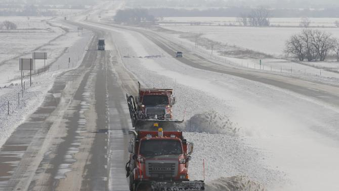 A pair of snow plows head west on US-54 Highway, clearing the snow off the roadway, near Cheney, Kan., Tuesday, Feb. 26, 2013. The second major snowstorm in a week battered the nation's midsection Tuesday, dropping a half-foot or more of snow across Missouri and Kansas and cutting power to thousands.  Gusting winds blew drifts more than 2 feet high and created treacherous driving conditions for those who dared the morning commute.  (AP Photo/The Wichita Eagle, Bo Rader)