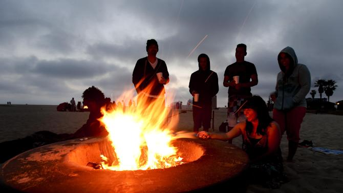 Beach goers stand around a fire pit on, Sunday, April 28, in Huntington Beach, Calif. Air quality regulators are considering a proposal to ban beach bonfires in Southern California due to health concerns. (AP Photo/Chris Carlson)