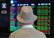 A retiree watches stock prices fall in Sydney. US stocks gave up early gains on positive US economic data to sink lower Wednesday as worries over Greece&#39;s future in the eurozone hit investor sentiment