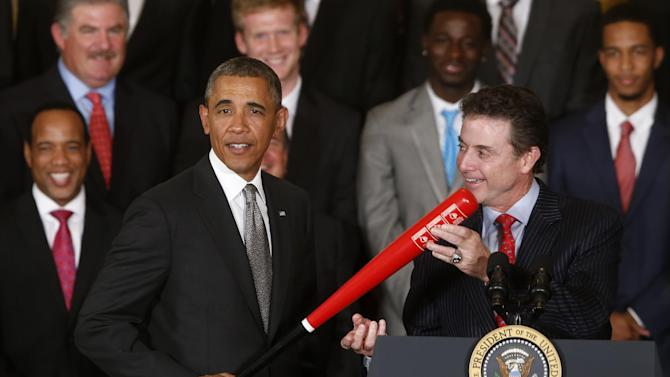 President Barack Obama holds up a Louisville Slugger baseball bat presented to him by Louisville basketball coach Rick Pitino, right, as he honored the 2013 NCAA Men's Basketball Champions Louisville Cardinals, Tuesday, July 23, 2013, in the East Room at the White House in Washington. (AP Photo/Charles Dharapak)