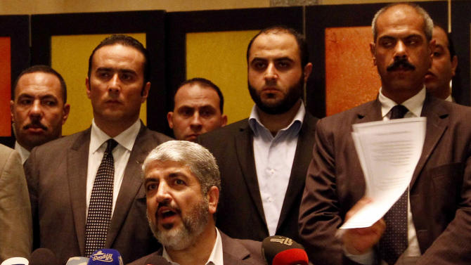 Hamas leader Khaled Mashaal holds a copy of the hamas-Israel cease-fire agreement during a press conference in Cairo, Egypt, Wednesday, Nov. 21, 2012. Israel and the Hamas militant group agreed to a cease-fire Wednesday to end eight days of the fiercest fighting in nearly four years, promising to halt air strikes and rocket attacks that have killed scores and to discuss easing an Israeli blockade constricting the Gaza Strip. Mashaal said the deal included an agreement to open all border crossings with the Gaza Strip, including the important Rafah crossing with Egypt. A copy of the deal obtained by The Associated Press appeared to be somewhat vague about the details on the crossings. (AP Photo/Ahmed Abd el Fatah)