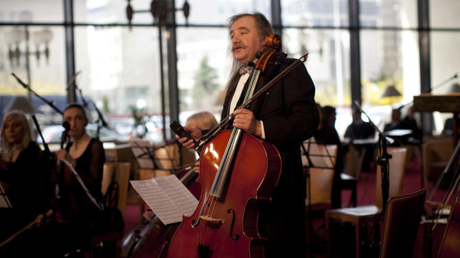 Bosnian musician Vedran Smajlovic addresses the auditorium before playing his cello at one of the ceremonies being held to mark the 20th anniversary of the start of the 44-month Bosnian Serb siege of Sarajevo, part of the 1991-95 Bosnian war, in  Sarajevo, Bosnia, Thursday, April 5, 2012. Twenty years ago, as mortar shells began raining down on Sarajevo, killing his friends and neighbors, Vedran Smajlovic did what he knew best to help the city: he played his cello at funerals, in bomb shelters and in the streets. (AP Photo/Anja Niedringhaus)