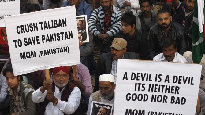 Supporters of Pakistan's Muttahida Quami Movement political party hold signs to condemn the Taliban attack on the Army Public School in Peshawar, during national solidarity rally Karachi