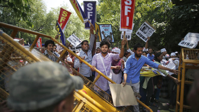 Indian students bring down a barricade during a protest near the Parliament in New Delhi, India, Monday, April 22, 2013. A second suspect was arrested Monday in the rape of a 5-year-old girl who New Delhi police said was left for dead in a locked room, a case that has brought a new wave of protests against how Indian authorities handle sex crimes. (AP Photo/Saurabh Das)