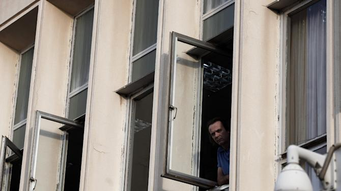 An employee at Greek state television ERT headquarters looks on from a window after the government's announcement that it will shut down the broadcaster in Athens, on Tuesday, June 11, 2013. Greece is to close down all its state-run TV and radio stations with the loss of some 2,500 jobs as part of its cost-cutting drive demanded by the bailed-out country's international creditors. Tuesday's move heralds the first direct public sector layoffs in more than three years of painful austerity, which have cost about a million private sector jobs. (AP Photo/Petros Giannakouris)