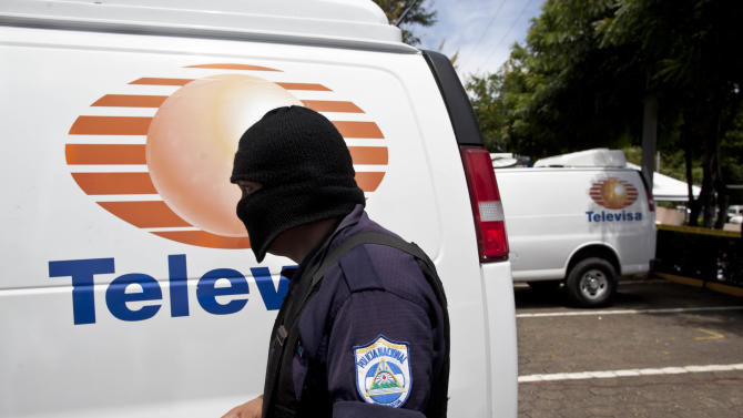 In this photo taken Wednesday, Aug. 29, 2012, a Nicaraguan police officer stands next to a van bearing the logo of Mexican news channel Televisa, confiscated from a group of Mexican nationals posing as journalists, in Managua, Nicaragua.  Nicaraguan police say the group was detained while attempting to drive the vans to Costa Rica, transporting millions of dollars, to pay for a load of drugs that had been smuggled into the United States. The Aug. 20 seizure has pulled back the curtain on Nicaragua's role as a conduit between South American cocaine producers and the Mexican drug cartels that move their product into the United States. (AP Photo/Esteban Felix)