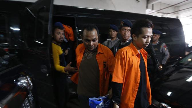 Indonesian policemen stand guard as Ahmad Junaedi and Aprimul Henry alias Mulbin Arifin, who are accused of supporting Islamic State, arrive for their trial at the West Jakarta court in Jakarta