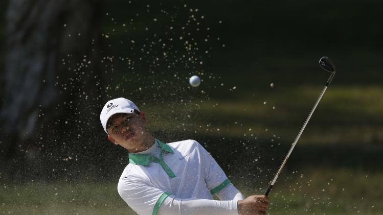 Guan of China hits from bunker during the first day of Hong Kong Open