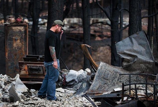 Jeremy Beach wipes away a tear as he sees his home off Ravine Drive West for the first time since the Black forest fire started last week, Tuesday, June 18, 2013, in Colorado Springs, Colo. Residents