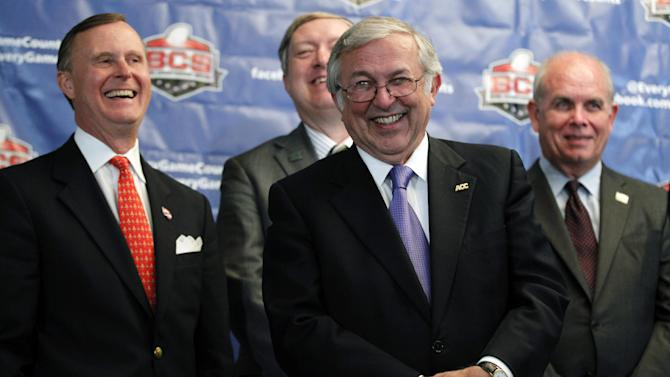 Charles Steger, center, president of Virginia Tech, smiles with Gary Ransdell, left, president of Western Kentucky, Duane Nellis, president of Idaho, and Bernie Machen, president of Florida, during a media availability after a BCS presidential oversight committee meeting, Tuesday, June 26, 2012, in Washington. A committee of university presidents on Tuesday approved the BCS commissioners' plan for a four-team playoff to start in the 2014 season. (AP Photo/Alex Brandon)