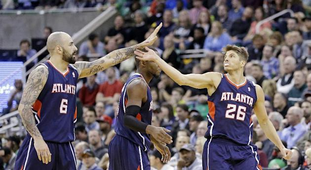 Atlanta Hawks' Pero Antic (6) high-fives Kyle Korver (26) in the fourth quarter during an NBA basketball game Monday, March 10, 2014, in Salt Lake City. The Hawks won 112-110