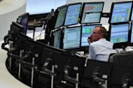 A trader sits in front of screens showing the German DAX index in Frankfurt in 2011. The eurozone crisis is increasingly hitting the German economy, the leader in Europe, data suggested on Monday as German business confidence fell for the fifth month in a row to the lowest level since February 2010