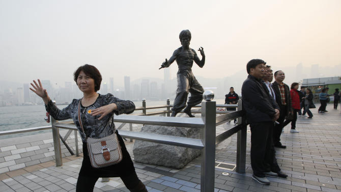 "In this Jan. 11, 2013 photo, Mainland Chinese tourists pose in front of a bronze statue of the Hong Kong martial art actor Bruce Lee on the Avenue of Stars, the city's version of the Hollywood Walk of Fame in Hong Kong. He's arguably Hong Kong's most famous movie star but the city has done little to commemorate Bruce Lee, who shot to global stardom with films like ""Enter the Dragon"" but died in 1973 at age 32 of swelling of the brain. (AP Photo/Kin Cheung)"