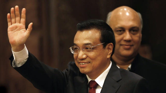 Chinese Premier Li Keqiang waves as he leaves after attending an event organized by Indian Council of World Affairs (ICWA), in New Delhi, India, Tuesday, May 21, 2013. Keqiang is on a three-day visit to India to discuss bilateral and trade ties. In the background is Indian Chambers of Commerce and Industry (FICCI) Vice President Sidharth Birla. (AP Photo/ Saurabh Das)