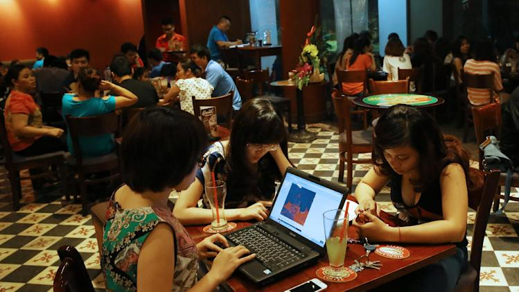 Three young Vietnamese girls use a laptop and smart phones to go online at a cafe in Ha Noi, Viet Nam Wednesday, May 14, 2013. Close to a third of Vietnam's 90 million people are online and men and women browsing phones and tablets are ubiquitous in the cafes of its towns and cities. The country's potential for growth, young population and good Internet infrastructure have made it an attractive destination for regional and international investors and startups in content provision, e-payment and other services. (AP Photo/Na Son Nguyen).