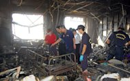Police and firemen inspect a badly damaged room following a fire at Sinying Hospital near the southern Taiwanese city of Tainan. An elderly man has been taken into custody for allegedly starting the fire that killed 12 people and injured 60, a prosecutor said Wednesday