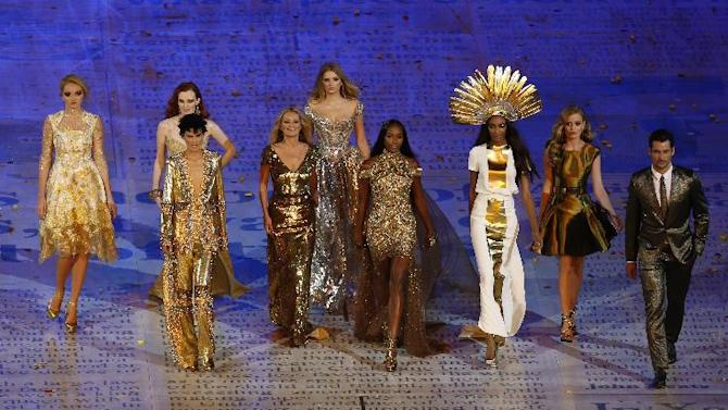 FILE - This Sunday Aug. 12, 2012 file photo shows models, from left, Lily Cole, Karen Elson, Stella Tennant, Kate Moss, Lily Donaldson, Naomi Campbell, Jourdan Dunn and Georgia May Jagger walking with a male model during the Closing Ceremony at the 2012 Summer Olympics in London. Gold was the new black at the closing ceremony with a parade of supermodels wearing gilded gowns in a tribute to British fashion. Kate Moss and Naomi Campbell both had on Alexander McQueen, Georgia May Jagger's was by Victoria Beckham, Karen Elson was in Burberry, and Stella Tennant donned a Christopher Kane Swarovski-crystal catsuit. (AP Photo/Alastair Grant, file)