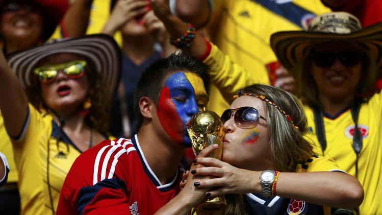 Colombia fans kiss a trophy during the 2014 World Cup Group C soccer match between Colombia and Ivory Coast at the Brasilia national stadium