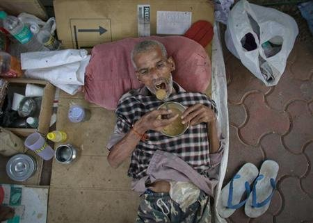 Parmeshwar Pujari, a 62-year-old cancer patient eats food while lying on the pavement outside the Tata Memorial Hospital in Mumbai March 4, 2013. REUTERS/Danish Siddiqui