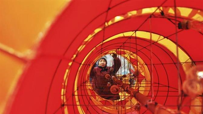 An employee works on a dragon lantern at a traditional lantern factory for the coming Chinese Lunar New Year, in Zibo, Shandong province, January 14, 2013. REUTERS/China Daily/Files