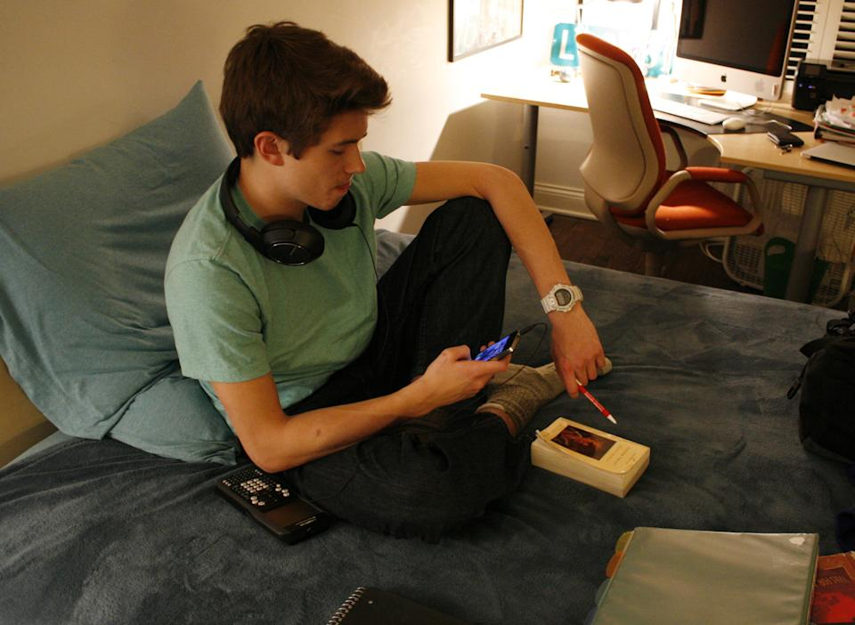 Donald Conkey, 15, checks his smartphone while doing homework in his bedroom on Monday, March 11, 2013, in Wilmette, Ill. A new report from the Pew Internet & American Life Project says more teens are using smartphones as a main means of accessing the Internet -- moreso than adults. (AP Photo/Martha Irvine)