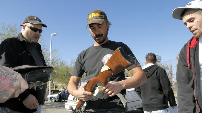 Gun buyers inspect their purchases outside a police station in Tucson, Ariz. on Tuesday, Jan 8, 2013. About a dozen buyers offered cash to sellers in the parking lot of a police station where Tucson City Councilman Steve Kozachik set up a gun buyback program in exchange for a $50 gift certificate to a grocery store. The buyers were trying to purchase weapons from sellers in an effort to circumvent Councilman Kozachik's buyback program. (AP Photo/Matt York)