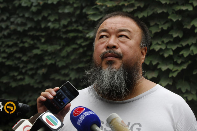 Dissident artist Ai Weiwei listens as his lawyer announces over a speakerphone the verdict of Ai's lawsuit against the Beijing tax authorities in Beijing Friday, July 20, 2012. A Beijing court on Frid