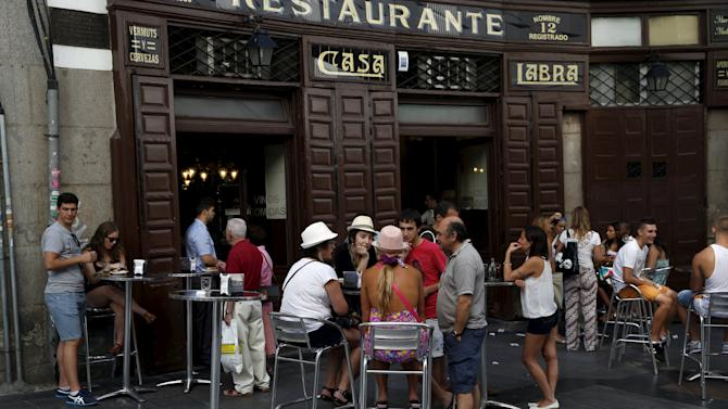 People fill the outside tables of a restaurant in central Madrid