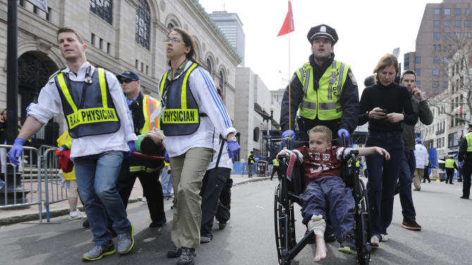 FILE - A Boston police officer wheels an injured boy down Boylston Street as medical workers carry an injured runner after two explosions during the 2013 Boston Marathon in Boston on Monday, April 15, 2013. (AP Photo/Charles Krupa)