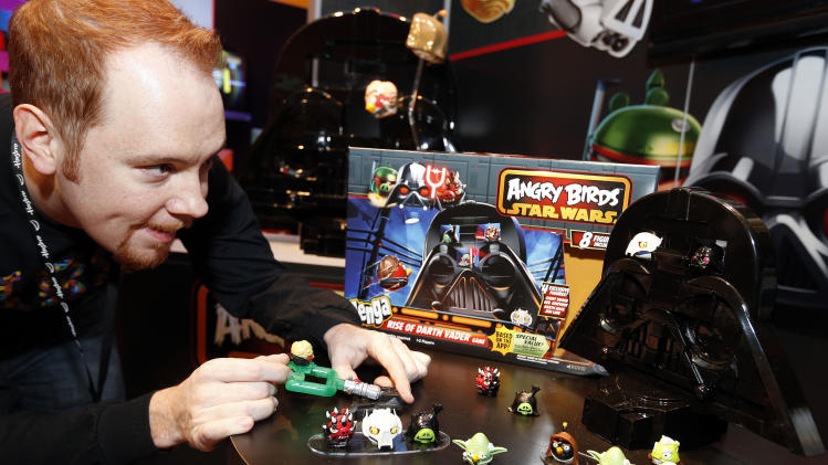 IMAGE DISTRIBUTED FOR HASBRO - Game demonstrator Jarrett Sullivan uses a light saber launcher at the ANGRY BIRDS™ STAR WARS® JENGA RISE OF DARTH VADER game, part of Hasbro's new line of ANGRY BIRDS™ STAR WARS® games, in the company's showroom at the American International Toy Fair, Monday, Feb. 11, 2013, in New York. (Photo by Jason DeCrow/Invision for Hasbro/AP Images)