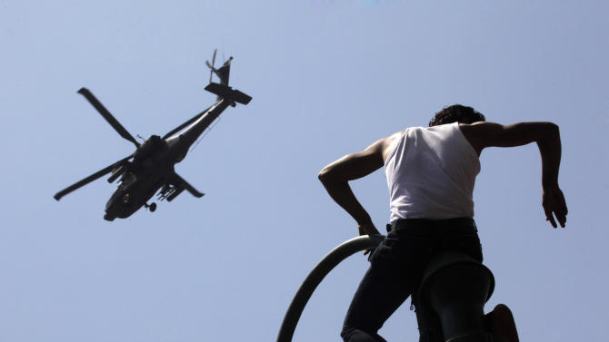 An Egyptian protester watches an Apache army helicopter is it flies over Tahrir Square, the focal point of Egyptian uprising, in Cairo Sunday, June 30, 2013. Organizers of a mass protest against Egyptian President Mohammed Morsi claimed Saturday that more than 22 million people have signed their petition demanding the Islamist leader step down, asserting that the tally was a reflection of how much the public has turned against his rule. (AP Photo/Amr Nabil)