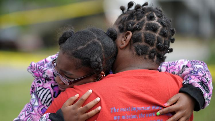 Brandy McCrary, left, a seven-year old cousin to five killed in a fatal house fire that included four children, is hugged by neighbor Bonita Beasley in Newnan, Ga., Saturday, April 27, 2013. The fire killed Alonna T. McCrary, 27, as well as her 5-year-old daughter Eriel McCrary and 2-year-old daughter Nikia White, according to Glenn Allen, the Georgia state Insurance commissioner's spokesman. Two other children, Messiah White, 3, and McKenzie Florence, 2, also died. Allen said the two were sleeping over at the home. A fifth child, 11-year-old Nautica McCrary, escaped the burning home and was taken to a hospital to be treated for smoke inhalation. (AP Photo/David Tulis)