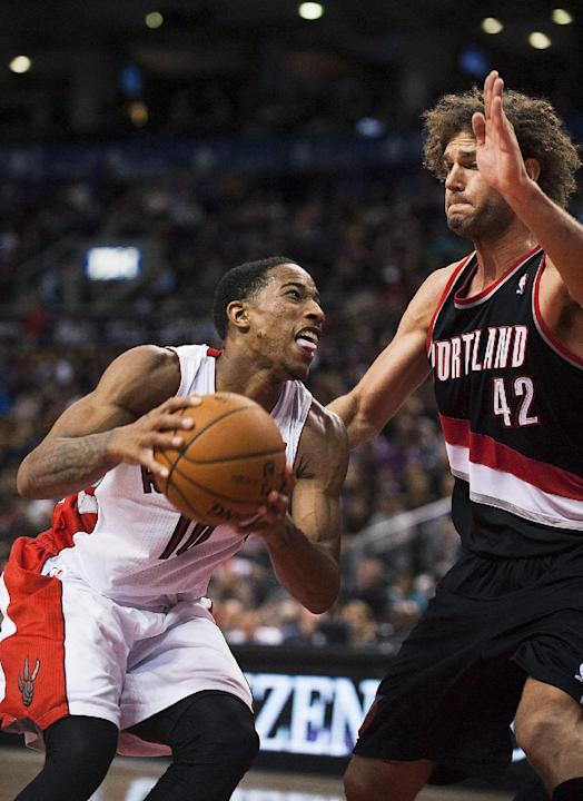 Toronto Raptors DeMar DeRozan drives to the basket against the Portland Trail Blazers Robin Lopez during an NBA basketball game in Toronto on Sunday, Nov. 17, 2013