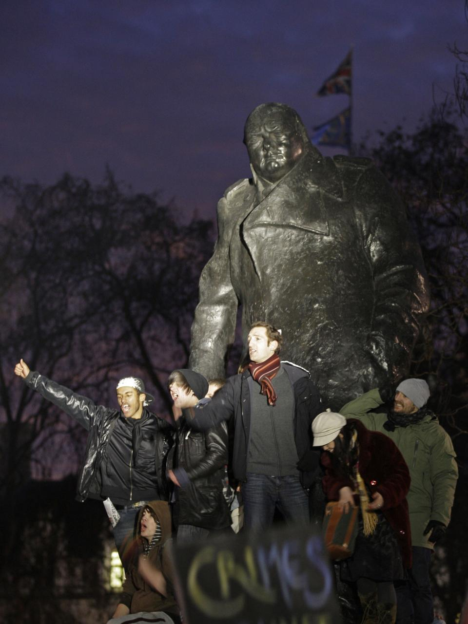 Protesters cry out as they stand on the statue of Winston Churchill at Parliament Square in London, as thousands of students demonstrate outside the Houses of Parliament in a protest against an increase in tuition fees, Thursday, Dec. 9, 2010. The House of Commons is to vote Thursday to increase tuition fees. (AP Photo/Sang Tan)