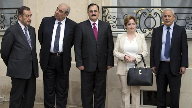 Members of the Syria National Coalition, from left, Farouk Tayfour, Michel Kilo, Salem Idriss, Suheir Atassi, and Burhan Ghalioun wait for the meeting of France's president Francois Hollande and Syria National Coallition president Ahmed al-Jarba at the Elysee Palace in Paris, France, Wednesday, July 24, 2013. (AP Photo/Francois Mori)