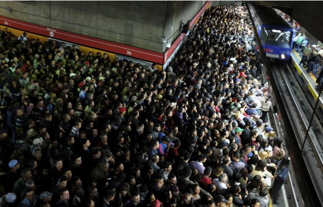 Commuters wait for the train at a subway station in downtown Sao Paulo