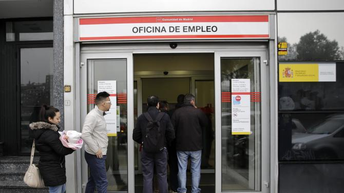 People stand in a line to enter a government employment office in Madrid