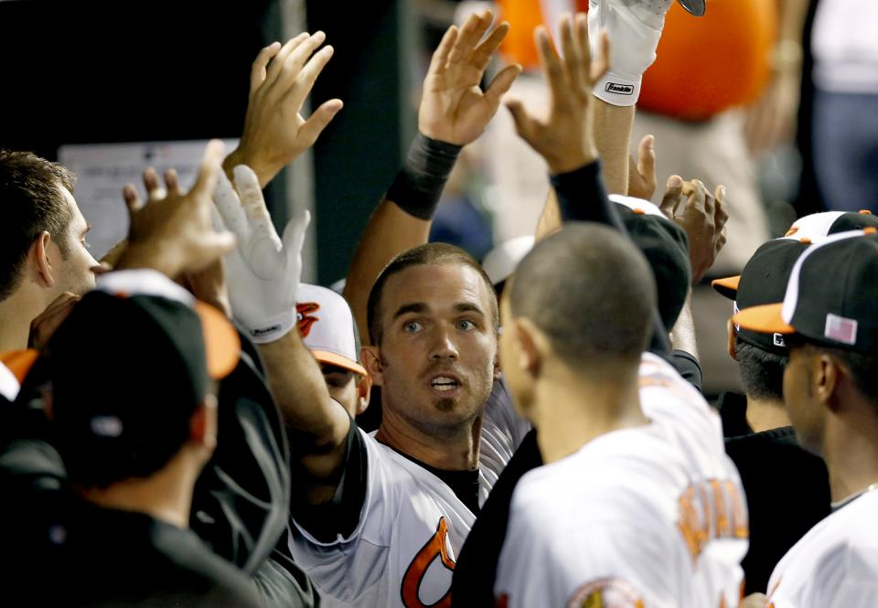 Baltimore Orioles' J.J. Hardy, center, high-fives teammates after hitting a two-run home run in the third inning of a baseball game against the Tampa Bay Rays in Baltimore, Tuesday, Sept. 11, 2012. (AP Photo/Patrick Semansky)