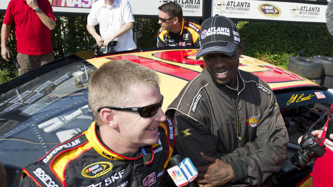 Cincinnati Bengals football player Chad Ochocinco and NASCAR Sprint Cup driver Jeff Burton talk with the media in victory lane after their high-speed laps in Burton's car at Atlanta Motor Speedway on Thursday, June 30, 2011. (AP Photo/Paul Abell)