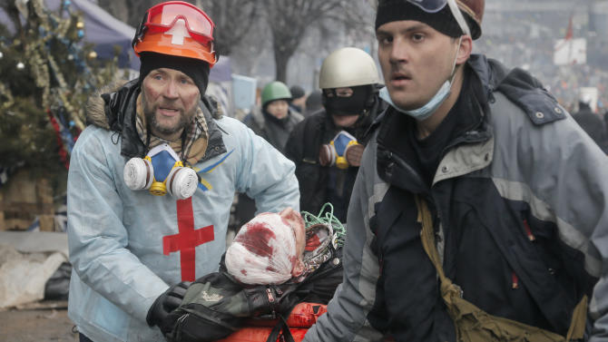 FILE- in this Thursday, Feb. 20, 2014 file photo, activists evacuate a wounded protester during clashes with police in Kiev's Independence Square, the epicenter of the country's current unrest, Kiev, Ukraine. As questions circulate about who was behind the lethal snipers that sowed death and terror in Ukraine's capital, doctors and others told the AP the similarity of bullets wounds suffered by opposition victims and police indicates the snipers were specifically trying to stoke tensions and spark a larger, angrier clash between opposition fighters and government security forces. (AP Photo/Efrem Lukatsky, file)