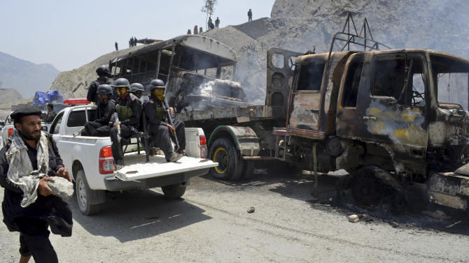 Pakistani tribal security personnel drive past gutted NATO trucks in Pakistan's tribal region of Khyber on Monday, June 10, 2013. A Pakistani official says a rocket attack targeting NATO supply trucks in the country's northwest has killed several people. (AP Photo/Qazi Rauf)
