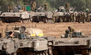 Israeli soldiers work on their tanks near the Gaza Strip, after fierce clashes with Gaza militants on Nov. 16.